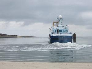 Ein Schiff startet im Hafen von Hörnum. Das Wasser erscheint trügerisch glatt.