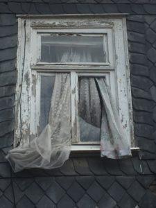 Fenster mit verschlissener Gardine