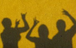3 Schatten vor gelber Wand