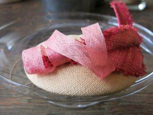 Ein Fascinator mit rosa Schnörkel
