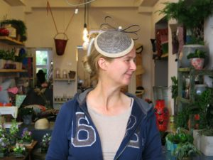 Katja Lux trägt einen grauen Fascinator