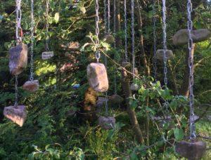 Steine an Ketten hängen vom Baum herunter