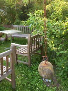 Holzstühle vor Büschen