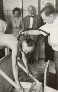 Ein Mann erhält beim Badejubiläum einen Wasserguss mit dem Schlauch