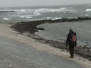 Ein Mann am Strand bei aufgewühlter See