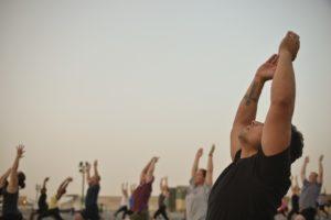 Männergruppe beim Sonnengruß beim Yoga