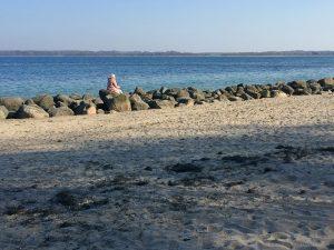 Eine Frau sitzt allein am Strand