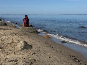 Eine Frau sitzt am Strand auf einem Stein