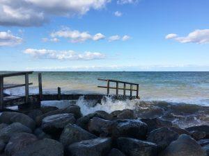 Kaputtes Geländer an einem Steg ins Meer