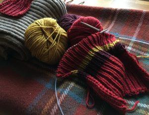 Strickzeug mit roter, brauner und gelber Wolle