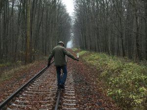 Ein Mann balanciert auf einer Bahnschiene