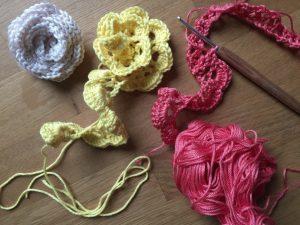 3 verschiedenfarbige Häkelrosen: weiß, gelb und rosa